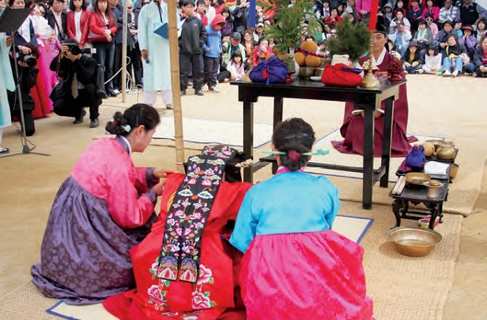 Traditional Wedding. The traditional Korean wedding ceremony largely consists of three stages: Jeonallye, in which the groom visits the bride's family with a wooden goose; Gyobaerye, in which bride and groom exchange ceremonious bows; and Hapgeullye, where the marrying couple share a cup of wine. The photo shows a bride and groom exchanging ceremonious bows during the Gyobaerye stage of their wedding ceremony.